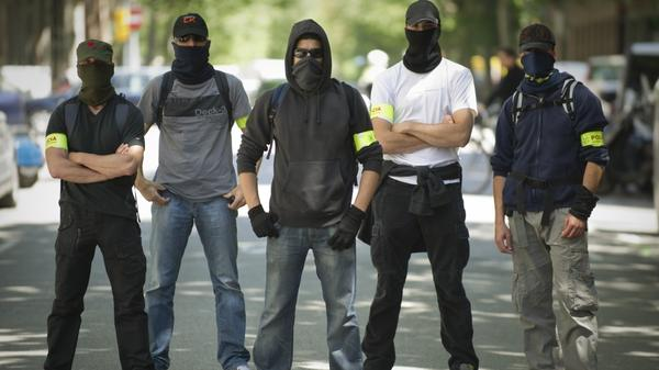 Undercover police stand on a Barcelona street during Thursday's demonstration against austerity cuts. On the same day, the European Central Bank's governing council met there but offered no relief to painful austerity measures.