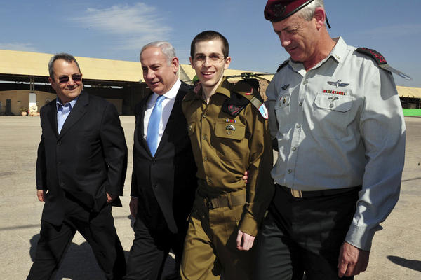 Released Israeli soldier Gilad Shalit, (second right), walks with Israeli Prime Minister Benjamin Netanyahu, (second left), Defense Minister Ehud Barak, and Israeli Chief of Staff Lt. Gen. Benny Gantz, on Tuesday. Schalit returned home  from more than five years of captivity in the Gaza Strip.