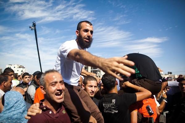 A Palestinian prisoner is held aloft in the West Bank city of Ramallah. He was one of 477 freed Tuesday, with 550 more to be freed in several months.