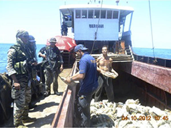 Filipino naval personnel look at giant clam shells onboard a Chinese fishing vessel at the disputed Scarborough Shoal in the South China Sea last month. Both countries claim the area, but say they are seeking a diplomatic solution.