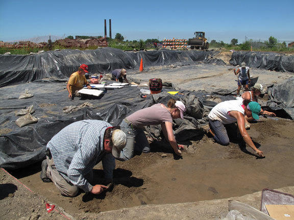 Illinois State Archaeological Survey crew members scrape the soil in search of Cahokian artifacts. The crumbling smokestacks of a 19th century meat packing plant are visible in the background, along with a bulldozer working on the current interstate freeway construction.