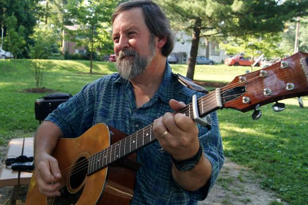Bruce Day, the president of CABOMA, plays his acoustic guitar.