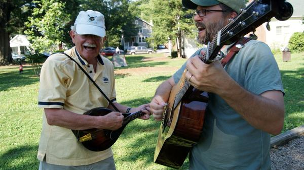 CABOMA members play guitar and mandolin on a summer afternoon.