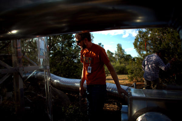 Powers looks in on a climate-controlled tree chamber. Silvery hoses carry heated air into the chambers.