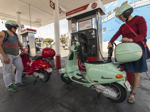 Motorcyclists Hanna Gilan, right, and her son Chaim Gilan fill up their Vespa scooters with less than two gallons at a gas station in the Echo Park district of Los Angeles on Oct. 4, 2012.