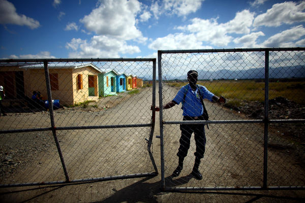 An armed guard keeps watch over a new, USAID-funded housing complex. The homes will be offered to people who work at Caracol.
