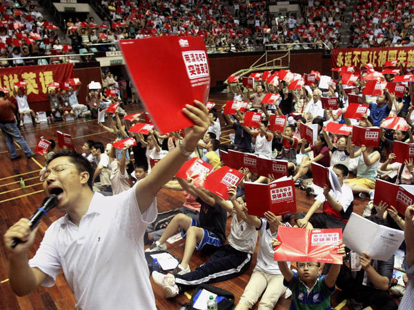 """Li Yang teaches English to several thousand students attending a class at a stadium in Guangzhou, China, in 2004. His """"Crazy English"""" technique — based on learning through shouting — draws huge crowds. In interviews, he has admitted physically attacking his wife."""