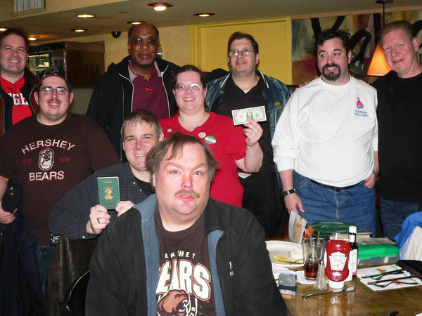 "Avid users of <a href=""http://wheresgeorge.com"">wheresgeorge.com</a> gather at Kabooz's Bar and Grill at New York's Penn Station to trade dollar bills and send off a group that's going on a cross-country train trip to Los Angeles."