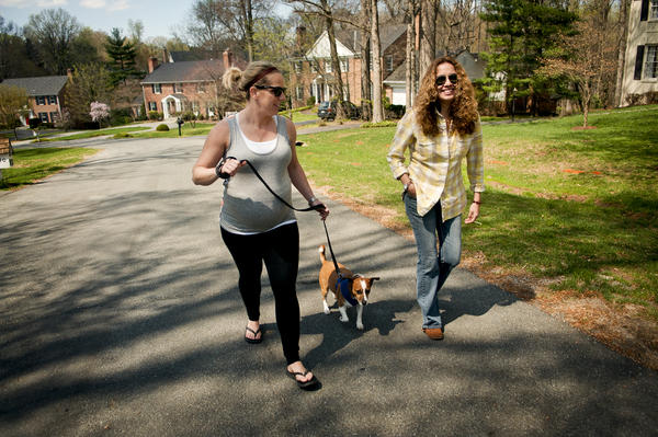 Kelly Costello, 31, (left) and her wife, Fabiola Morales, 39, walk their 4-year-old dog, Blue Elizabeth, around their neighborhood in Potomac, Md. The two have been married since 2012.