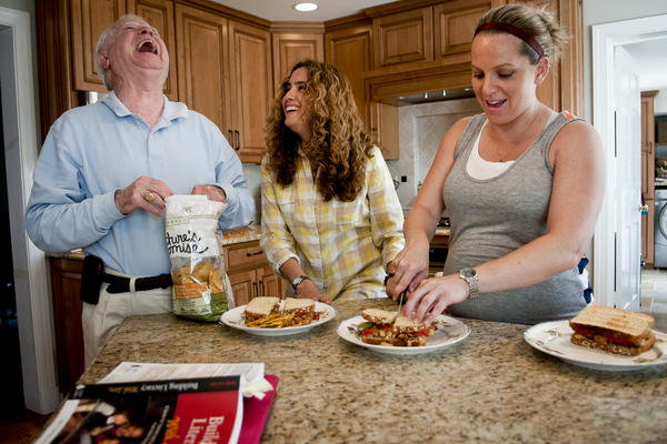 "Fabiola Morales jokes with her father-in-law, Robert F. Costello III, a retired financial adviser, while preparing lunch in the family's kitchen. Kelly Costello's dream is to be able to sponsor Morales and feel ""secure and stable."""
