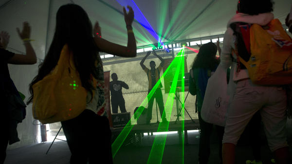 People dance in laser lights in a tent during World Youth Day events in Quinta de Boa Vista park, where religious orders are holding a job fair of sorts to recruit new postulants.