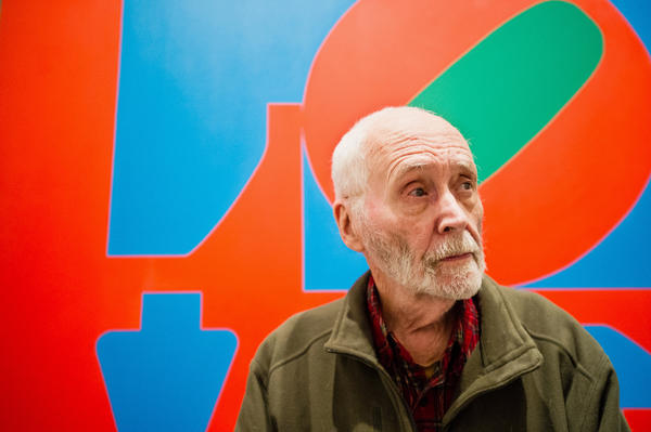 Robert Indiana first emerged as a pop artist in the early 1960s, but he was quickly defined by his 1966 signature work, <em>LOVE</em>, shown behind Indiana in this 2013 photo.