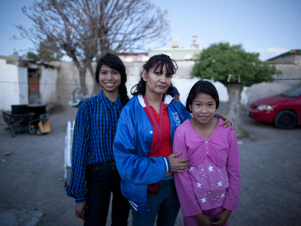 Yvonne Navarro stands outside her home with her two daughters. Navarro works in a factory making parts for refrigerators and other appliances, which are shipped across the border to the U.S.