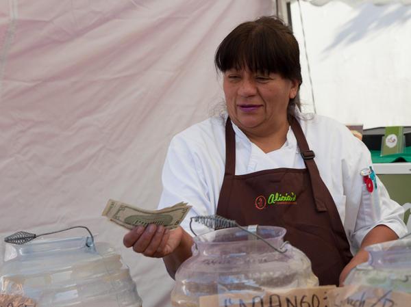 Alicia Villanueva gives change to a customer at Off the Grid, a weekly street-food market in San Francisco.
