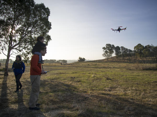David Merrill and his son play with one of his drones in a park.