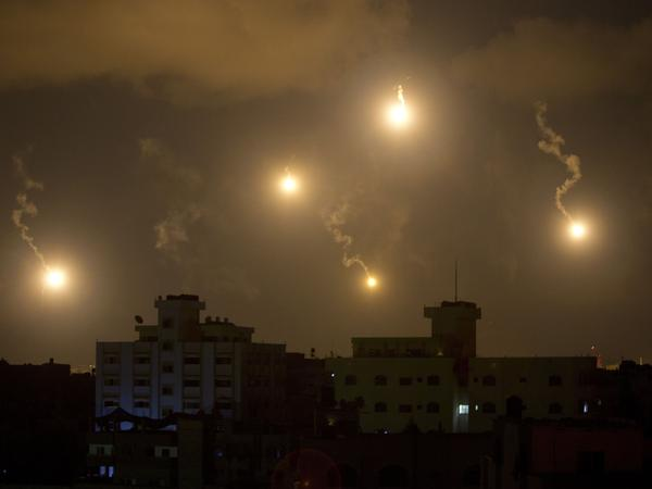Israeli army flares illuminate the sky above the Gaza Strip on Friday. At least three people, including two children, ages 4 and 7, were killed by Israeli tank fire in Gaza, medics said.