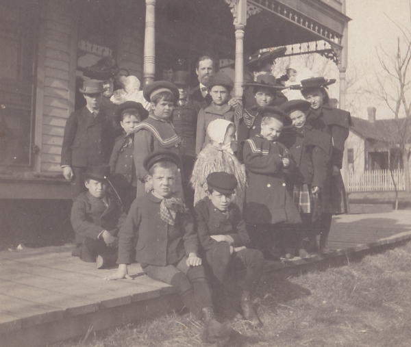 Children's Aid Society placement agents Anna Laura Hill (back row, right, wearing a large hat), H.D. Clark and Mrs. Clark (back row, left) with a company of children.