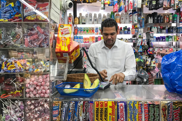 Merquis Garcia works A & M Supermarket's counter, where customers can pick up slices of fresh avocado and candied pineapple.
