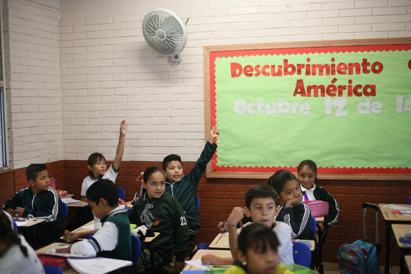 Students raise their hands at the Escuela 20 Noviembre school in Tijuana, Mexico.