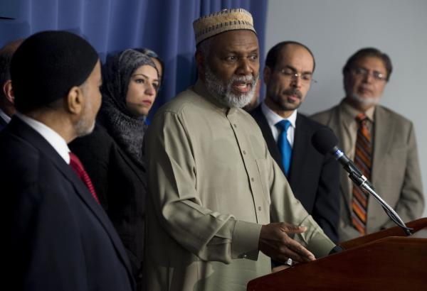 "Imam Johari Abdul-Malik (center), of Dar Al-Hijrah Islamic Center in Northern Virginia, speaks alongside other leaders of the Muslim community during a December 2015 news conference in Washington, D.C., about growing ""Islamophobia"" in the United States."