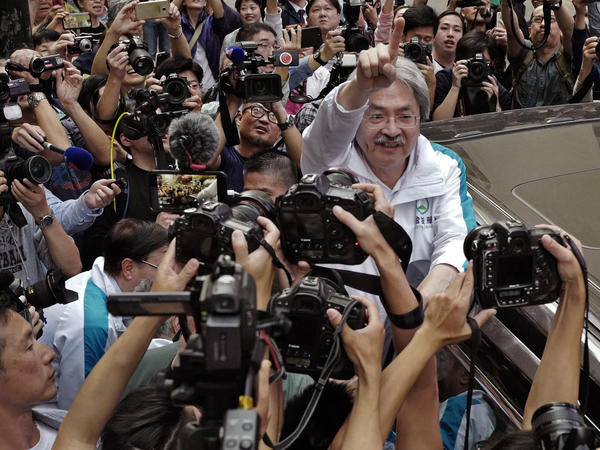 Chief Executive candidate John Tsang waves to supporters in Hong Kong on Friday. Nearly all public opinion polls show he is the most popular candidate and would likely win if there were to be a citywide vote.