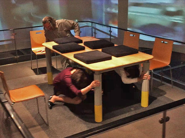 Visitors at the Tokyo Fire Department's Ikebukuro Life Safety Learning Center take cover under a table as the center's earthquake simulator begins shaking violently.
