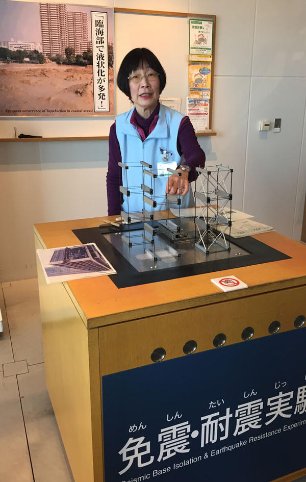 Volunteer docent Nanami Yoshimoto demonstrates earthquake-resistant building design for throngs of daily visitors at the Disaster Reduction Institution in Kobe.