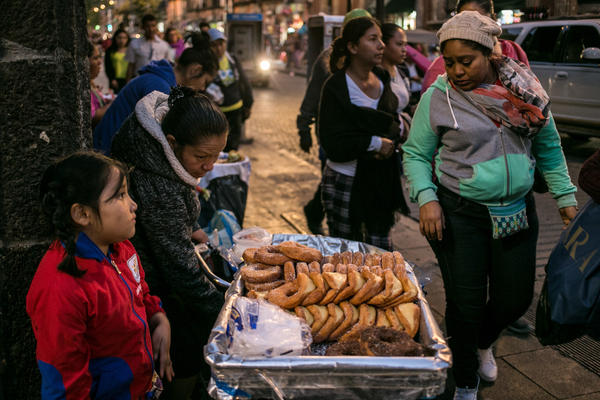 A family sells pastries in Mexico City. As Mexicans' wages have risen, their average daily intake of calories has soared.