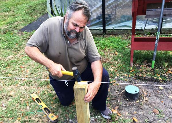 Marine Corps veteran Bernie Lodico straightens one of the fence posts in the Veterans Garden.