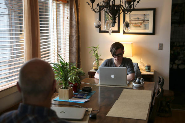 <p>Skylar Isaacs (right) takes online classes as a high school junior at one end of the dining room table. His father Steven often sits across fromhim.</p>