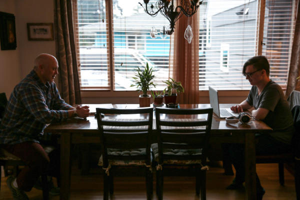 <p>Skylar Isaacs (right) takes online classes as a high school junior at one end of the dining room table. His father Steven often sits across from him.</p>