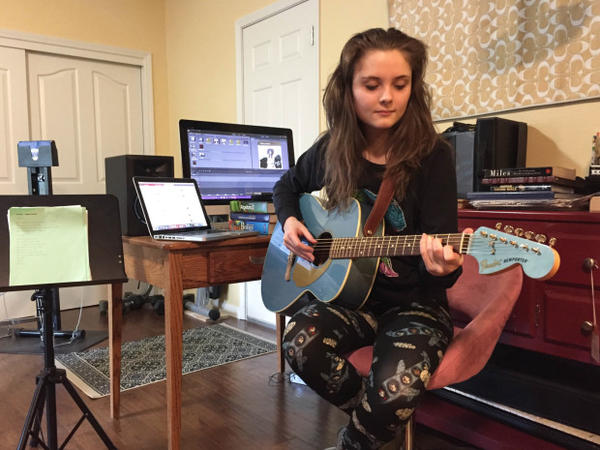 <p>Josephine Relli plays guitar in the family basement, which serves as her classroom and music studio. She's a student at an online charter school, Oregon Connections Academy.</p>