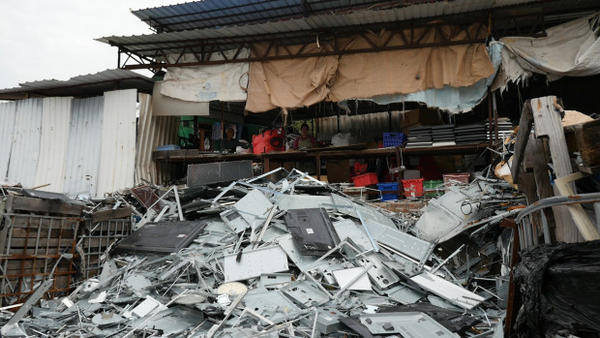 """<p><span class=""""s1"""">A pile of scraps from dismantled flatscreen televisions sits in front of workers at a junkyard in Hong Kong. Using a GPS location tracker, the environmental group Basel Action Network tracked a television from the Seattle-based recycler Total Reclaim to this junkyard.</span></p>"""