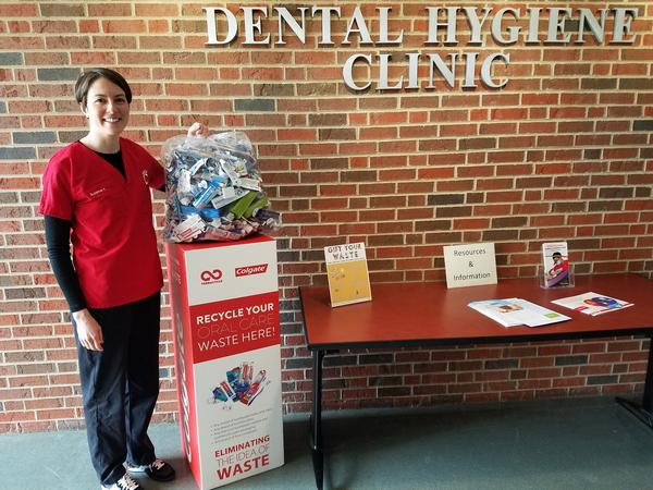 Dental hygiene student Suzanne Yorke stands with a 10 pound bag of dental waste ready to be recycled into benches and picnic tables.