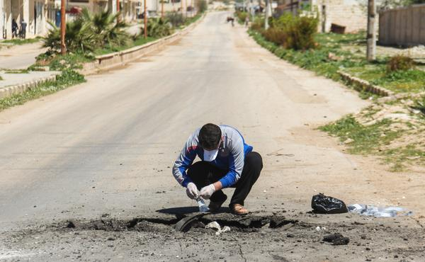 A man collects samples Wednesday from the site of a suspected toxic chemicals attack in Khan Shaykhun the day before.