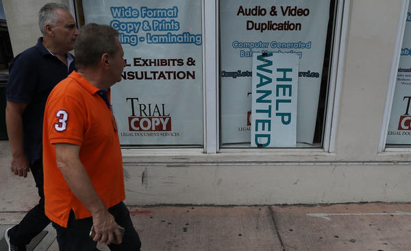 "A ""help wanted"" sign hangs in a storefront window in Miami last month. The Bureau of Labor Statistics says nonfarm payrolls increased by 98,000 in March, far below analysts' expectations."