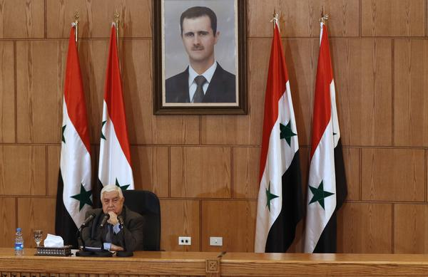 At a press conference in Damascus on Thursday, Syrian Foreign Minister Walid Muallem denied that government forces had used chemical weapons. A portrait of Syrian President Bashar Assad is seen hanging on the wall behind him.