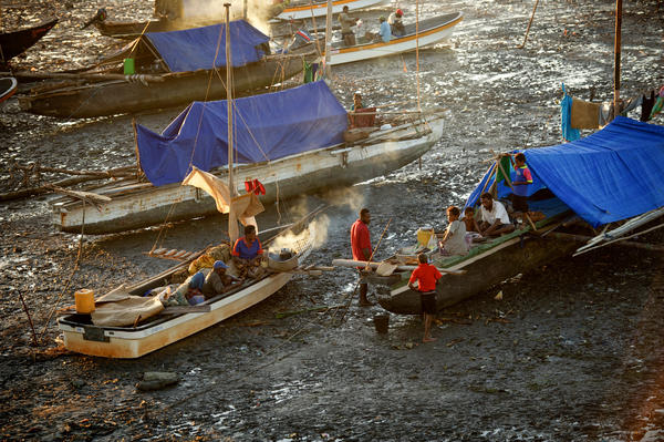 Fishermen in Papua New Guinea, living on their boats, wait for the tide to change before going out to fish. Tuberculosis is a major health threat in the Pacific Ocean nation.