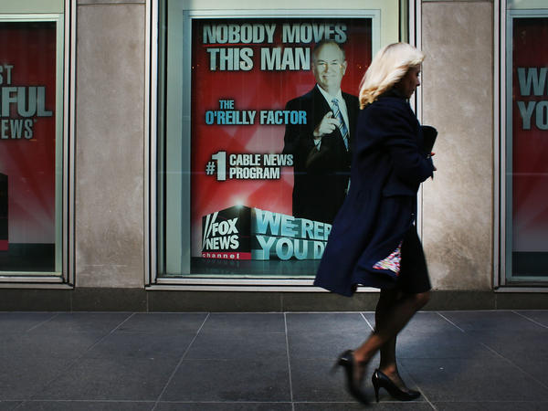 An ad for Bill O'Reilly's top-rated Fox News show stares back at passersby outside the News Corp. headquarters in New York City earlier this month. O'Reilly is stepping away from the show for a vacation as controversy continues to mount around sexual harassment claims.