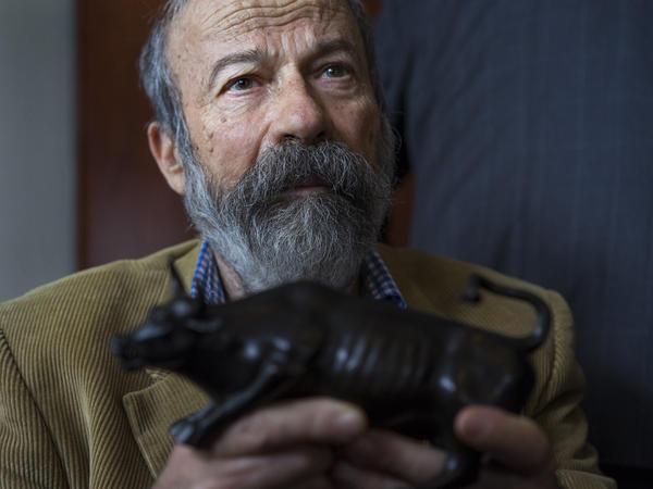 Arturo Di Modica holds a model of his <em>Charging Bull</em> during a news conference Wednesday.