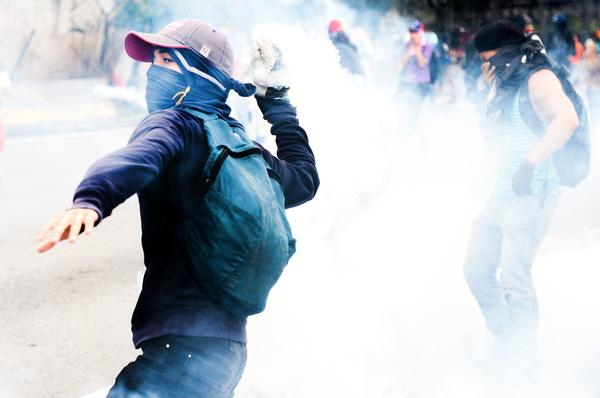 Opposition activists clash with riot police during protests Thursday. By the end of the day, a man had died of his gunshot wounds, bringing the number of people killed in past two weeks of protests to five.