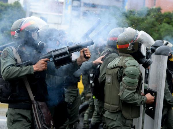 Riot police march on the protesters in the streets of Caracas on Thursday.