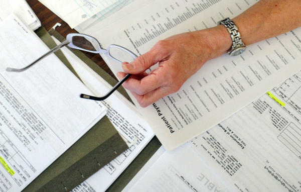 <p>In this Dec. 20, 2011, file photo, medical bills are spread out on the kitchen table of a patient in Salem, Virginia. A new report found that some medical debt collection agencies use aggressive tactics to collect debts from patients that aren't actually owed.</p>