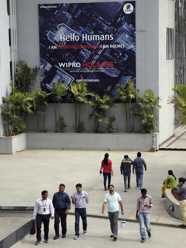 Wipro Ltd. employees walk inside the company's compound in January during a break at their headquarters in Bangalore, India. Top Indian IT companies are in the crosshairs of proposed changes to U.S. H-1B visas, including an executive order President Trump is expected to sign Tuesday.