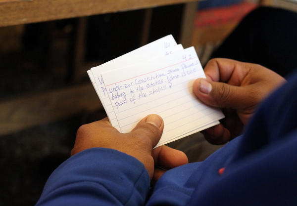 A student uses notecards to learn facts about American government during a class at the public library in Brush, Colo.