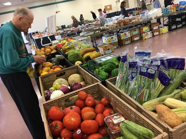 A volunteer with the Saddleback Church prepares produce as part of the group's food pantry at Camp Pendleton. The church typically serves about 100 active duty military families as part of its monthly food pantry.