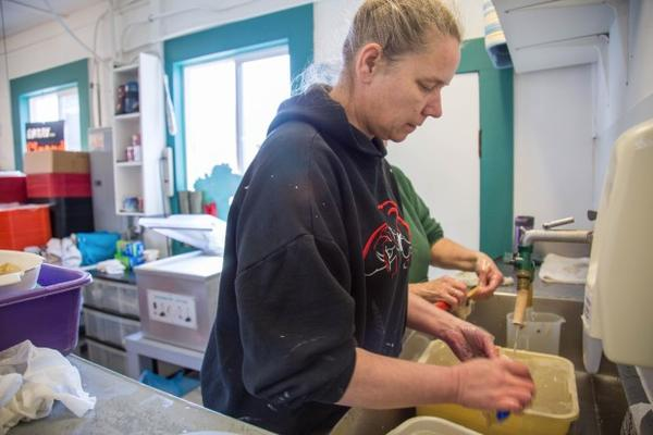 <p>Tina Ward, co-owner of Sportsmen's Cannery, cleans buckets of razor clams dropped off by customers.</p>