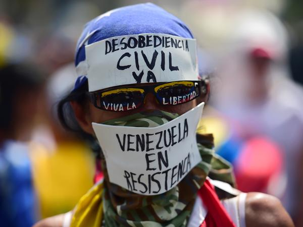 A demonstrator against Venezuelan President Nicolas Maduro's government wears a mask calling for civil disobedience during a protest in Caracas on Wednesday.