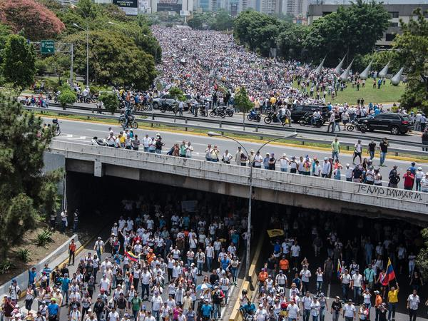 Demonstrators clog a Caracas highway on Wednesday, shouting their resistance to Maduro. The president's push to tighten his power has helped trigger deadly unrest in Venezuela.