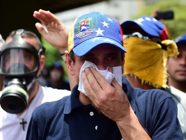 Opposition leader Henrique Capriles, who was banned from public office for 15 years, protects himself against tear gas during a rally against Maduro on Wednesday.